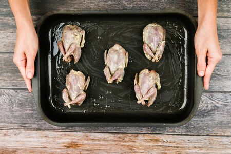 Quail on a wooden background. Quail baking on a baking sheet. cooking quail. Lies on the forehead, in front of the oven. close-up. hands in cooking.