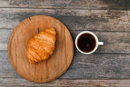 croissant e una tazza di caffè sul tavolo. Croissant francese fresco. su uno sfondo di legno. Vista dall'alto. Colazione mattutina con croissant. Colazione francese Ottima fatta in casa. Torre fresca