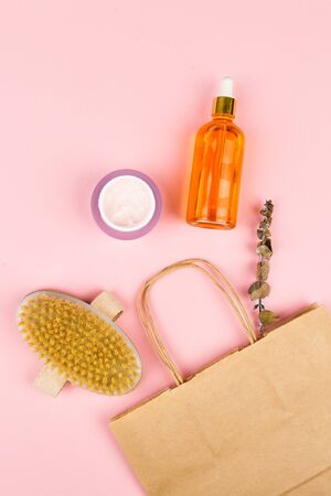 Ecological packaging for skin care. Anti-cellulite massage brushes. view from above. Massage brush. Accessories for massage. Flatley. Eco care concept. Skin care products. craft paper. Body care natural wood products eco friendly on pink background. Zero waste concept.