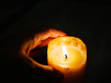 Candle in the hands on a dark background. during the festival of light.