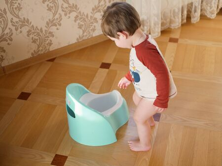 The boy and the potty. Adorable baby girl playing with a chamber pot at the living room. Adorable baby girl playing with a chamber pot on the floor at the living room. studying the restroom for the child