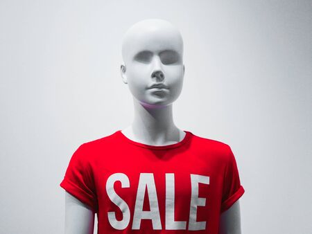 Female mannequin in a shop window on the background of the inscription sale