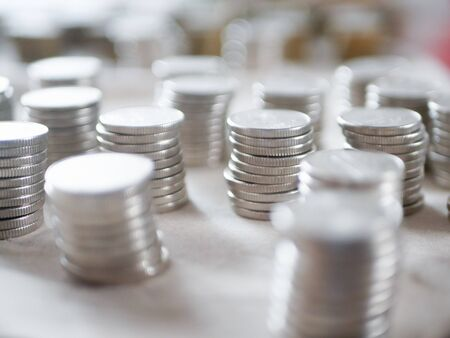 Silver coins close up. Counting savings. Tax rate. Production costs. Distribution of finance. Laid out by a column.