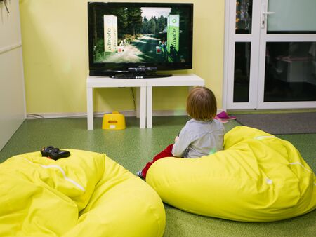 A child plays a game console alone. plays video games