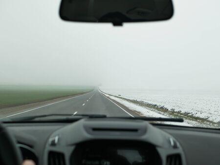 El coche se adentra en la niebla. vista frontal. conducción insegura. El coche va rápido en la carretera en la niebla, vista desde el habitáculo. Foto de archivo