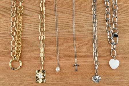 Gold and silver handmade chains. on a wooden background. Ornaments from decorative chains. Materials for handmade and hobby. Colorful background of silver and gold chains