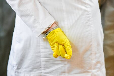 White bathrobe and yellow gloves. Girl with a hand in the back. Unsuitable medical worker. Medical training 写真素材