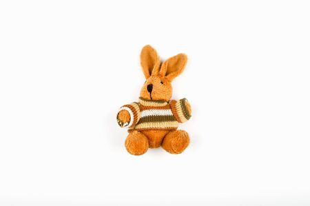 Brown plush hare on a white background. Old plush brown retro hare on white wall background Imagens