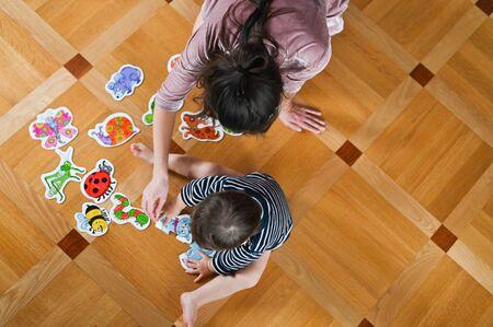Mama und Baby studieren Insekten. Mutter unterrichtet ein Kind. Sicht von oben. Baby und Insekten. Flach liegen. Standard-Bild