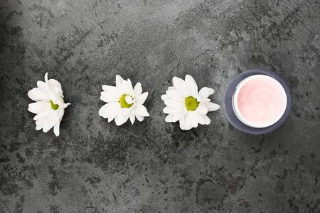 Flowers with a jar of cream on a dark marble background. View from above. Natural cosmetic