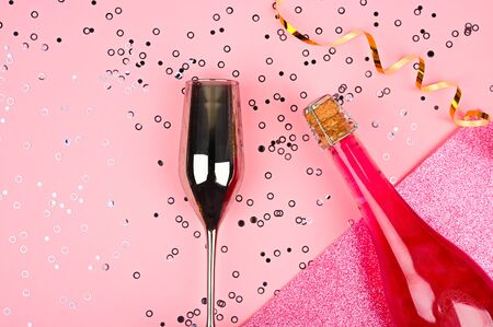 Champagne and holiday concept. Glass with sparkles on pink glitter background. Flat lay style