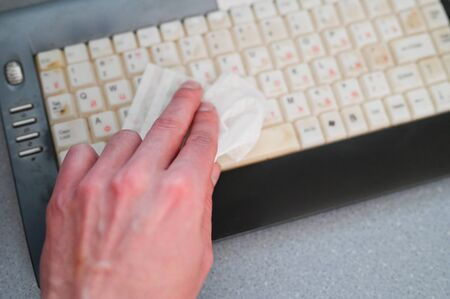 Person sanitizes a computer keyboard with antibacterial wipes. Close-up. Coronavirus Precautions concept.