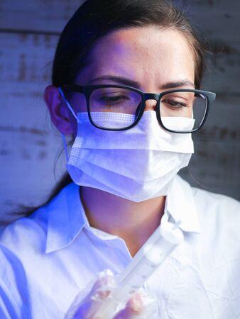 scientist works with harmful chemicals. A laboratory worker examines biologically hazardous liquids, hazardous work, chemistry. careful work