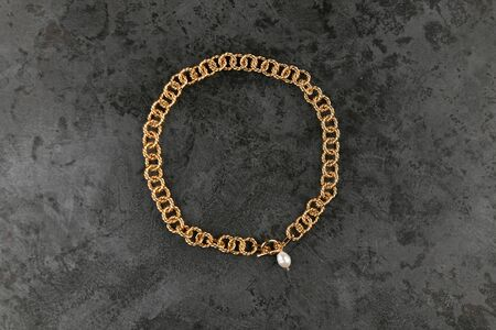 gold chain with pearls against black background. place for an inscription. golden chain on marble. ring gold plate Reklamní fotografie