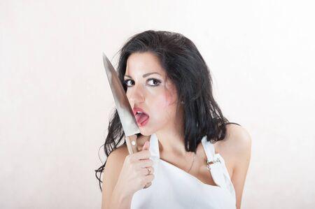 girl licks a knife. Brunette with a big knife