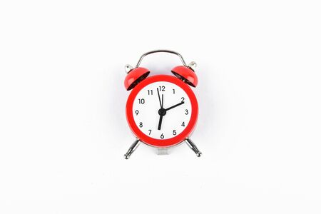 Red retro alarm clock on a white background.
