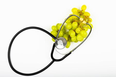 green grapes and health. on white background. view from above. A place to write. A bunch of green grapes. The concept of the usefulness of grapes