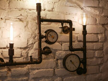 Steampunk decor. With iron pipes. and incandescent lamps. Loft style wall and steampunk pipes.