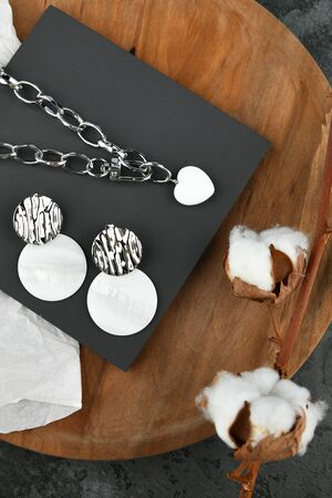 Set of silver jewelry with earrings. Heart-shaped pendant on a silver chain. Decorations for Valentine's Day. chains on a wooden background. View from above
