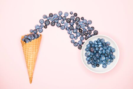 Fresh blueberries in ice cream cone on a pink background. Blueberry Blast. Summer vacation concept. Flat lay, top view. The style of natural organic food. hands picking blueberries