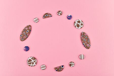A product from polymer clay. Hand sculpting, product for earrings on a pink background. View from above. Beige earrings with colorful patterns. Handmade polymer clay jewelry.