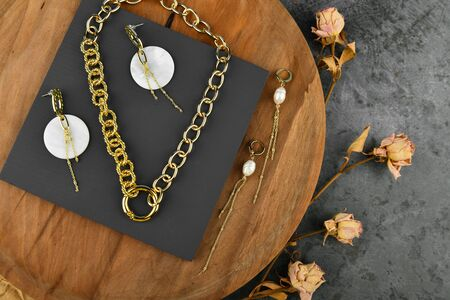 Handmade gold jewelry for women. Jewelry for all lovers. chains on a wooden background. View from above