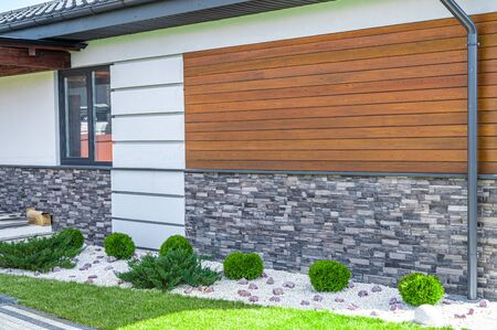 cladding of a house made of wood and decorative brick.