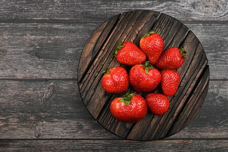 red strawberry lies on a wooden round plank. Imagens