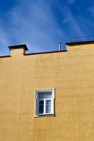 One window on a yellow building against a blue sky. High quality photo