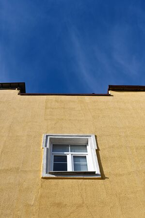 One window on a yellow building against a blue sky. High quality photo Stok Fotoğraf - 148182993