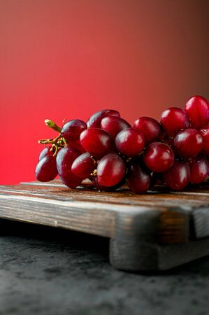 Red grapes on a red background. High quality photo