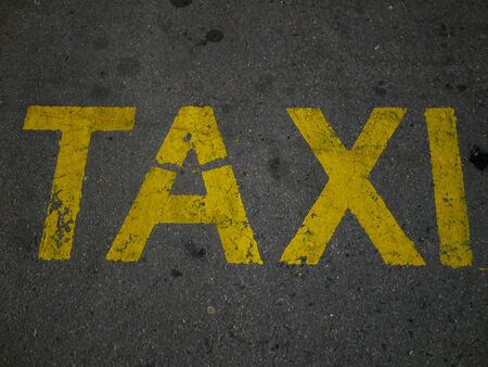 Yellow taxi inscription on the pavement. A place for parking and waiting for a taxi driver Zdjęcie Seryjne