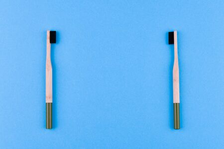 wooden toothbrush on a blue background. Close up wooden toothbrush on a blue background. eco brush