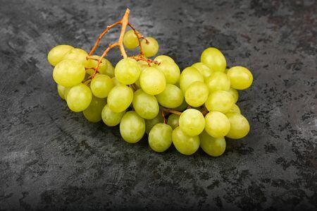Photo of green grape on a marble dark background. Volumetric grapes. A bunch of green grape bush Stok Fotoğraf