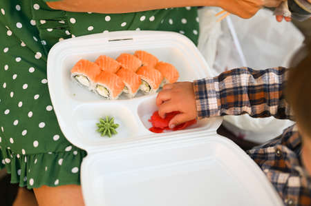 Mother with baby eat sushi on the street on the street. High quality photo