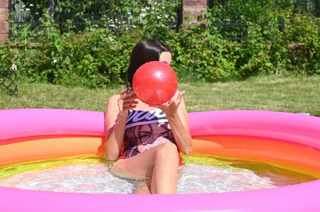 Girl and home inflatable pool. High quality photo Stock fotó