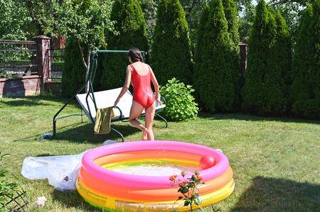 Girl and home inflatable pool. High quality photo