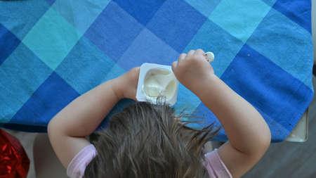 Baby boy eating a spoon top view of yogurt