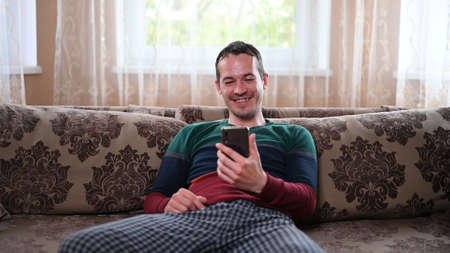 A man sits on a couch and talks through a mobile video call