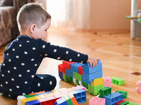 A child plays in a colorful constructor sitting on the floor. . High quality photo