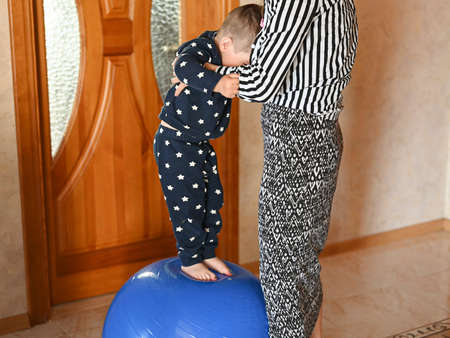 Mom does body exercises at home with her baby. Using a fitness ball. High quality photo