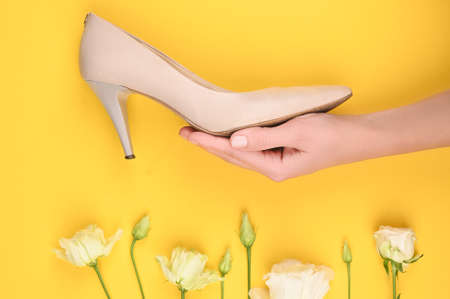 The concept of womens shoes. Womens beige shoes on a hand in flowers. on a yellow background. beige shoes on the hand for girls. Wallpaper and flowers. Place for writing.