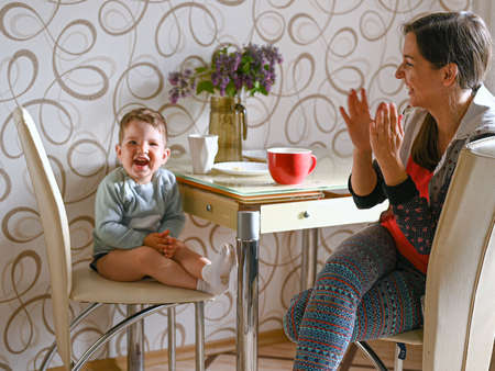 Mom with a child are sitting in the kitchen. Mom spends time with the child. Archivio Fotografico