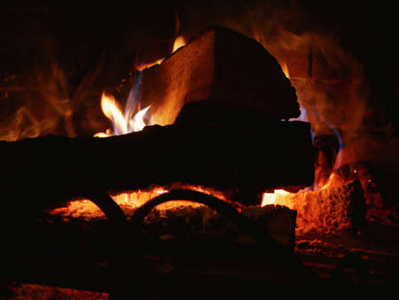 Fire in the fireplace in the dark. Burning logs in a fireplace. Imagens
