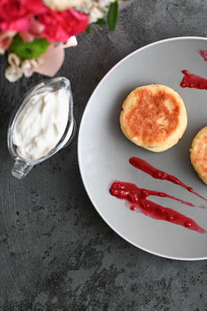 cheese pancakes with jam. on a gray background with flowers.