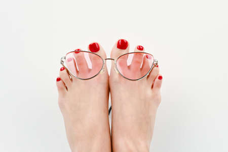 Vacation concept on the beach. feet in glasses on a white background close-up
