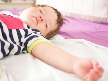 baby sleeps in parents bed. arms outstretched baby's restful sleep. close-up. child 0-1 years old. adorable lovely baby sleeps calmly in bed, has a pleasant healthy sweet dream, cared for. From affectionate parents. Imagens