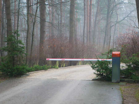 Closed forest barrier. Country road in the forest with a closed red white barrier. The protection of nature.