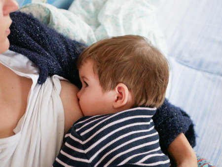 Mother is breastfeeding her baby. close-up. natural nutrition. Young mother breastfeeding her newborn baby boy at home.
