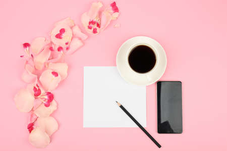 The concept of day planning. A cup of coffee, white card, pink flowers. Flat lay. Banque d'images